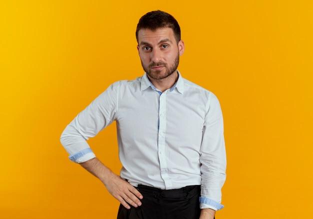 Pewnie przystojny mężczyzna kładzie rękę na talii na białym tle na pomarańczowej ścianie