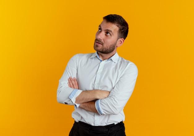 Pewnie przystojny mężczyzna krzyżuje ramiona patrząc na białym tle na pomarańczowej ścianie