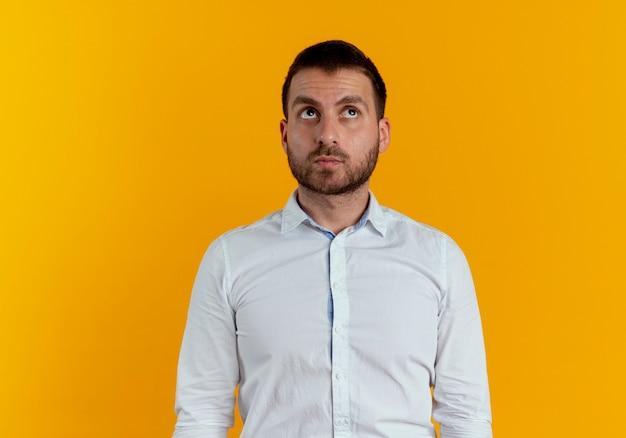 Pewnie przystojny mężczyzna patrzy na białym tle na pomarańczowej ścianie
