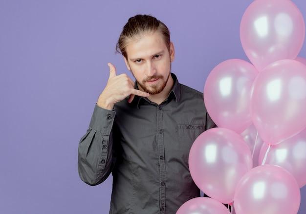 Pewnie przystojny mężczyzna trzyma balony z helem i gesty nazywają mnie ręką znak na białym tle na fioletowej ścianie