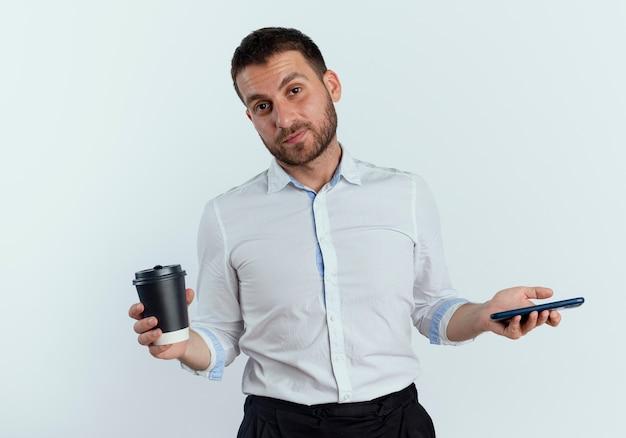 Pewnie przystojny mężczyzna trzyma filiżankę kawy i telefon na białym tle na białej ścianie