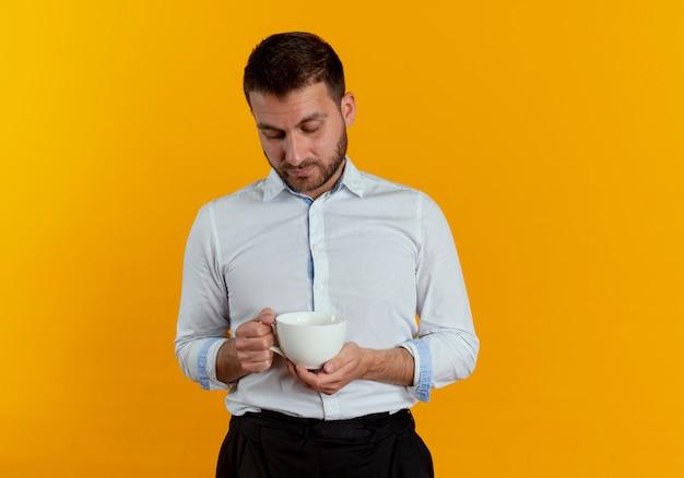 Pewnie przystojny mężczyzna trzyma i patrzy na kubek na białym tle na pomarańczowej ścianie