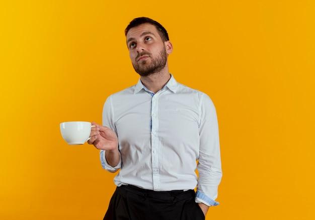 Pewnie przystojny mężczyzna trzyma kubek patrząc w górę na białym tle na pomarańczowej ścianie