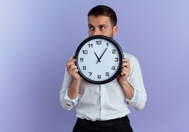 Pewnie przystojny mężczyzna trzyma zegar patrząc na bok na białym tle na fioletowej ścianie