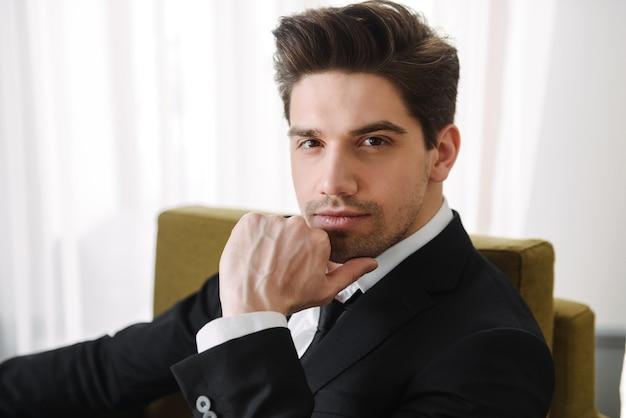 Pewnie przystojny mężczyzna ubrany w garnitur, siedząc w fotelu w pomieszczeniu