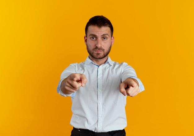 Pewnie przystojny mężczyzna wskazuje dwiema rękami na białym tle na pomarańczowej ścianie