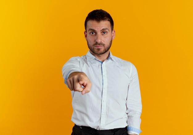 Pewnie przystojny mężczyzna wskazuje na białym tle na pomarańczowej ścianie