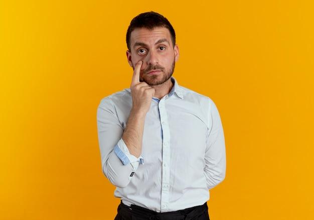 Pewnie przystojny mężczyzna wskazuje na oko na białym tle na pomarańczowej ścianie