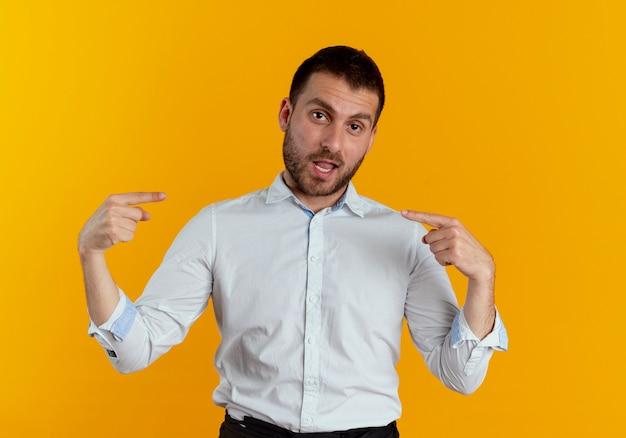 Pewnie przystojny mężczyzna wskazuje na siebie dwiema rękami odizolowanymi na pomarańczowej ścianie