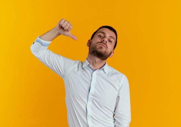 Pewnie przystojny mężczyzna wskazuje na siebie na białym tle na pomarańczowej ścianie
