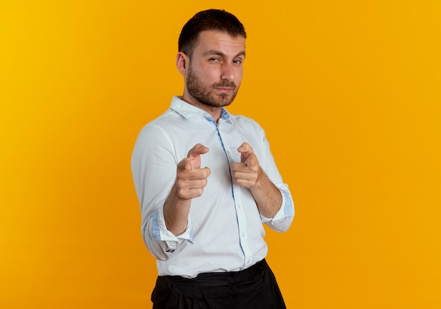 Pewnie przystojny mężczyzna wygląda i wskazuje dwiema rękami na białym tle na pomarańczowej ścianie