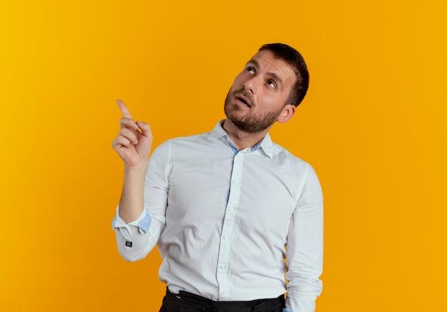 Pewnie przystojny mężczyzna wygląda i wskazuje na białym tle na pomarańczowej ścianie