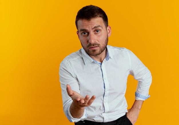 Pewnie przystojny mężczyzna wygląda i wskazuje ręką na białym tle na pomarańczowej ścianie