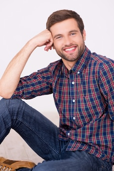 Pewnie przystojny. przystojny młody mężczyzna uśmiechający się i opierając głowę na dłoni, siedząc na podłodze
