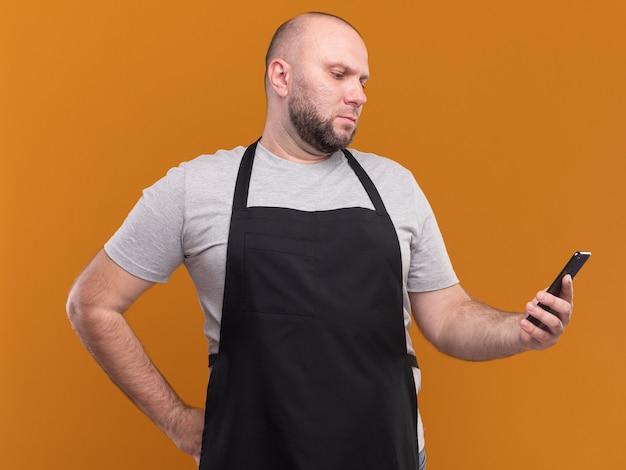 Pewnie słowiański mężczyzna w średnim wieku fryzjer w mundurze, trzymając i patrząc na telefon, kładąc rękę na biodrze na białym tle na pomarańczowej ścianie