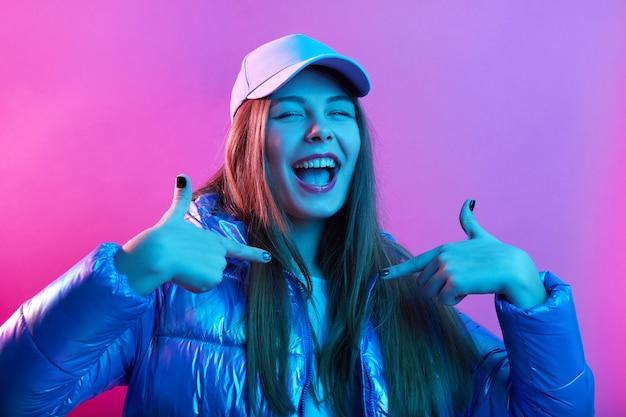 Pewnie szczęśliwa podekscytowana kobieta nosi kurtkę i czapkę baseballową
