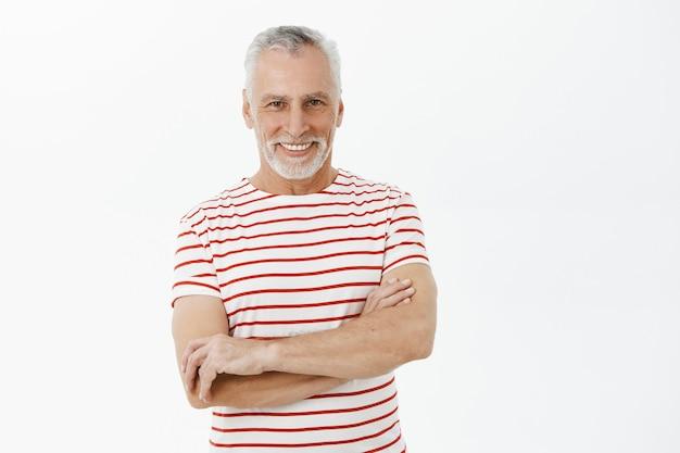 Pewnie uśmiechnięty dziadek krzyżuje ramiona w klatce piersiowej i wygląda na szczęśliwego