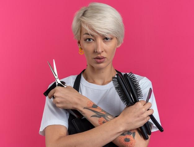 Pewnie wyglądający młody piękny fryzjer żeński w mundurze trzymający narzędzia fryzjerskie izolowane na różowej ścianie