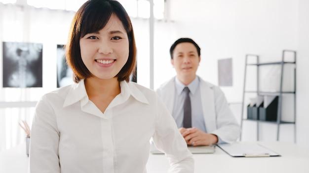 Pewność azji mężczyzna lekarz w białym mundurze medycznym i młoda dziewczyna pacjenta patrząc na kamerę i uśmiechając się podczas konsultacji lekarskiej przy biurku w klinice lub szpitalu.