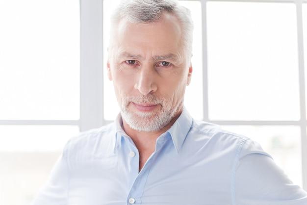 Pewność siebie i sukces. pewny siebie starszy mężczyzna z siwymi włosami w koszuli patrzący na kamerę stojąc przed oknem