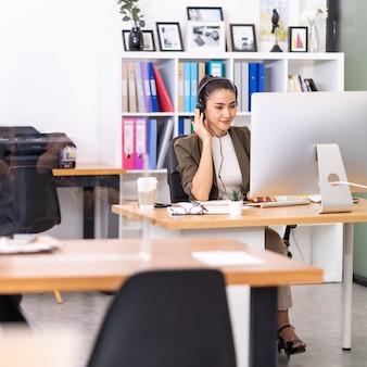 Pewność siebie młoda dorosła azjatka ze słuchawkami pracująca w call center z tabelą odległości społecznej jako nowa normalna praktyka. koncepcja sprzedaży call center i telemarketingu.