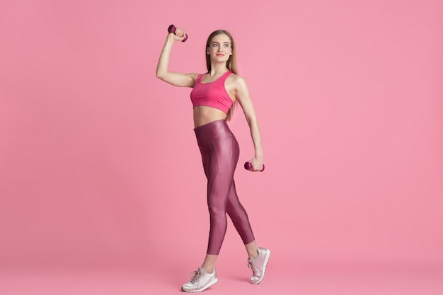 Pewność siebie. piękna młoda lekkoatletka praktykujących, monochromatyczny różowy portret. sportowy krój kaukaski model z ciężarkami. koncepcja budowy ciała, zdrowego stylu życia, piękna i działania.