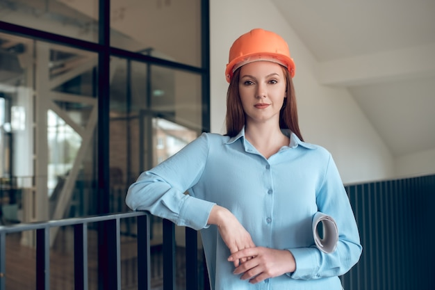 Pewność siebie. szczęśliwa pewna siebie, długowłosa kobieta w pomarańczowym kasku ochronnym i jasnoniebieskiej bluzce stojącej z planem budowy w pomieszczeniu