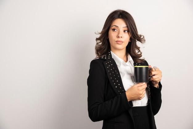 Pewny biznes pozujący z filiżanką herbaty