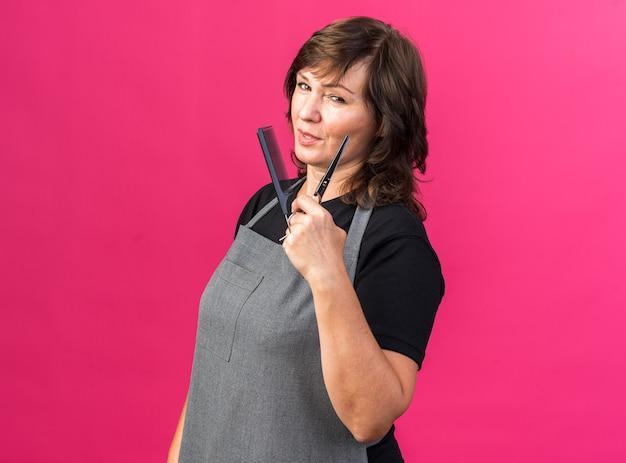 Pewny dorosły kaukaski fryzjer żeński w mundurze stoi bokiem trzymając grzebień i nożyczki na białym tle na różowym tle z kopią przestrzeni