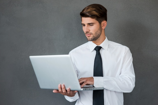 Pewny Ekspert Biznesowy. Pewny Siebie Młody Człowiek W Koszuli I Krawacie Pracujący Na Laptopie Premium Zdjęcia