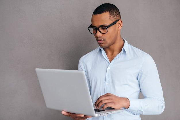 Pewny ekspert it. pewny siebie młody afrykanin pracujący na laptopie