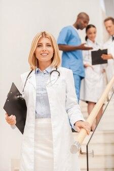Pewny ekspert medyczny. pewna siebie lekarka schodzi na dół i uśmiecha się, podczas gdy jej koleżanki rozmawiają w tle
