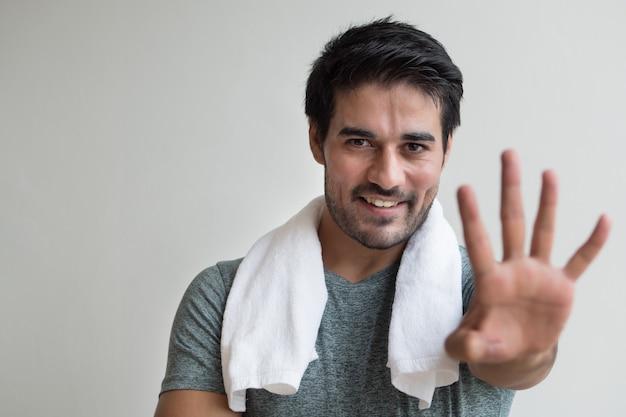 Pewny fitness mężczyzna wskazując cztery palcem w górę; portret szczęśliwego, zdrowego, pewnego siebie, przyjaznego fitness azjatyckiego mężczyzny wskazującego znak palcem numer 4 lub gest dłoni; azjatycka północna indyjska dorosły mężczyzna modelka