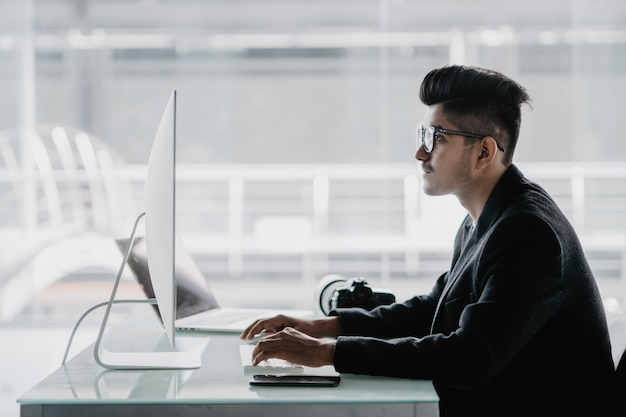 Pewny fotograf. wesoły młody człowiek trzyma aparat cyfrowy i uśmiecha się siedząc w swoim miejscu pracy
