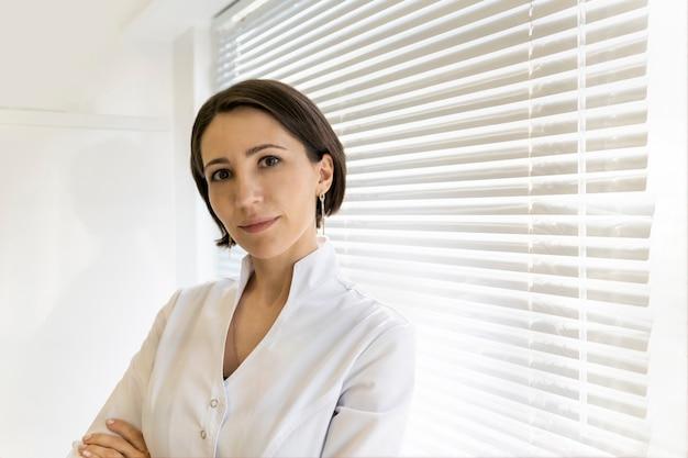 Pewny lekarz w białej szacie siedzi uśmiechając się, kobieta pracownik medyczny w białej szacie patrzy w kamerę
