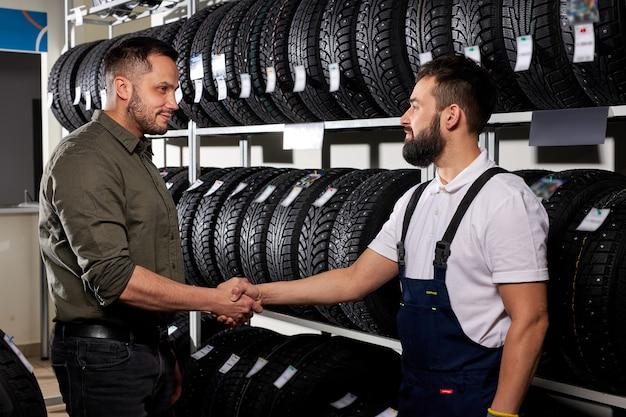 Pewny mechanik mechanik ściska rękę klientowi, sprzedawca pomaga przy wyborze opony w sklepie