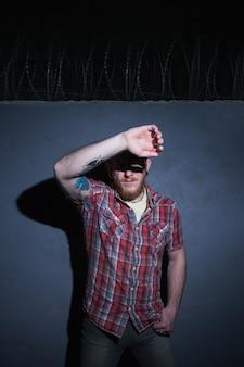 Pewny mężczyzna więzień. jasne światło na twarzy. hipster człowiek na niebieskim tle, kryminalny facet w nocy, koncepcja więzienia
