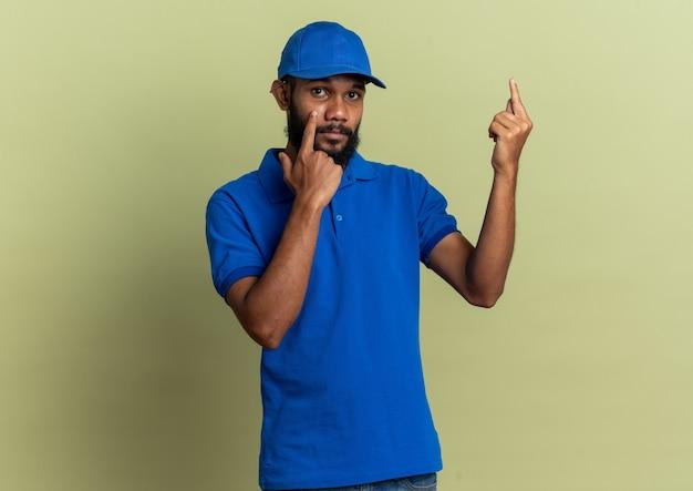 Pewny młody afro-amerykański mężczyzna dostawy, ciągnąc w dół jego powiekę i wskazując w górę na białym tle na oliwkowo-zielonym tle z kopią przestrzeni