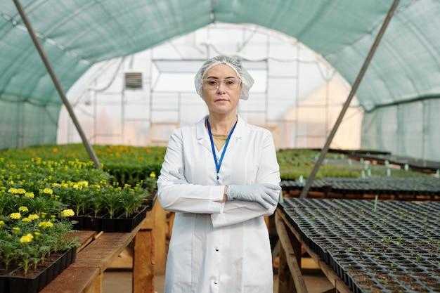 Pewny naukowiec w dziedzinie odzieży ochronnej stojącej przy stołach z rosnącymi sadzonkami