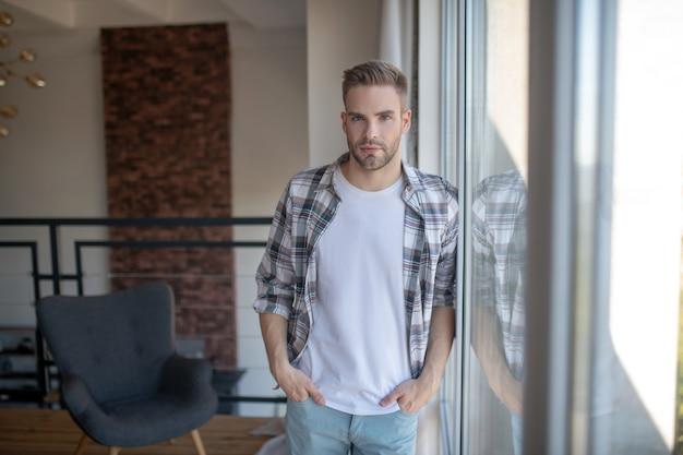 Pewny portret. pewny siebie przystojny mężczyzna stojący w pobliżu panoramicznego okna