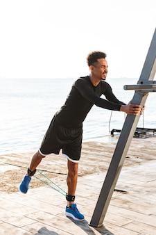 Pewny siebie afro amerykański sportowiec ćwiczący z ekspanderem na świeżym powietrzu na plaży