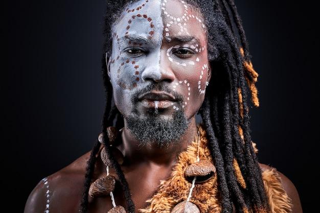 Pewny siebie afrykański aborygen na białym tle nad czarną ścianą, z kolorowymi etnicznymi rysunkami na twarzy