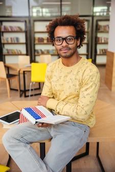 Pewny siebie afrykański młody człowiek w okularach, czytanie książki w bibliotece