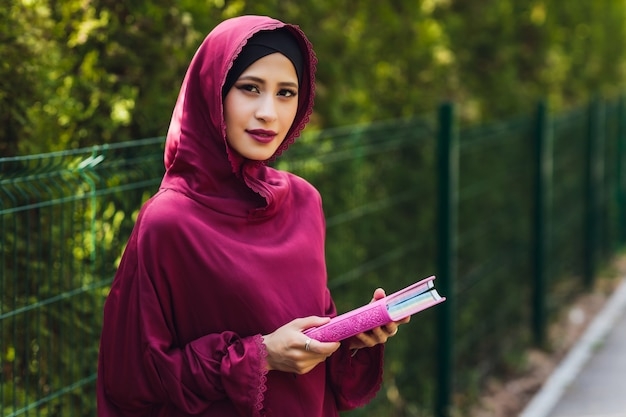 Pewny siebie arabski biznesmen uśmiecha się i spacery po dubaju arabski biznes vumen hidżab jest na ulicach przed drapaczami chmur w dubaju kobieta jest ubrana w czarną abaję