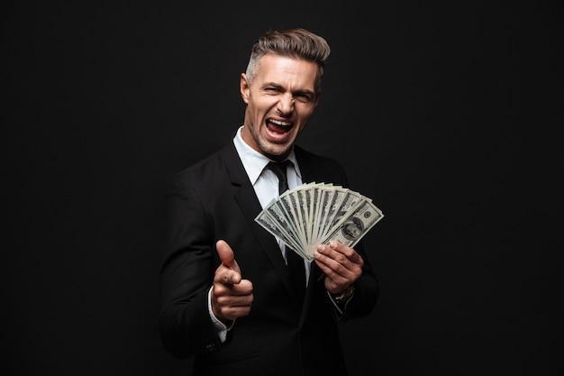Pewny siebie, atrakcyjny biznesmen w garniturze stojący na białym tle nad czarną ścianą, pokazujący banknoty, wskazujący palec
