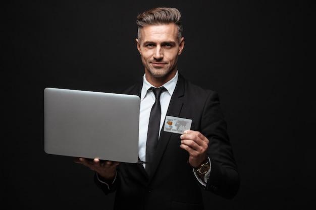 Pewny siebie, atrakcyjny biznesmen w garniturze, stojący na białym tle nad czarną ścianą, używający laptopa, pokazujący plastikową kartę kredytową