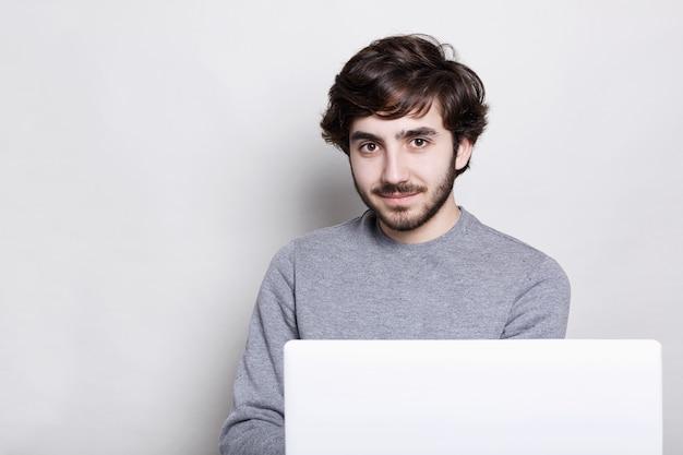 Pewny siebie atrakcyjny facet z ciemną brodą i stylową fryzurą siedzi przed otwartym laptopem