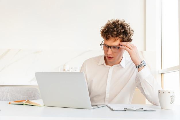 Pewny siebie, atrakcyjny młody biznesmen ubrany w białą koszulę, pracujący na laptopie, siedząc przy stole w domu, popijając kawę z kubka