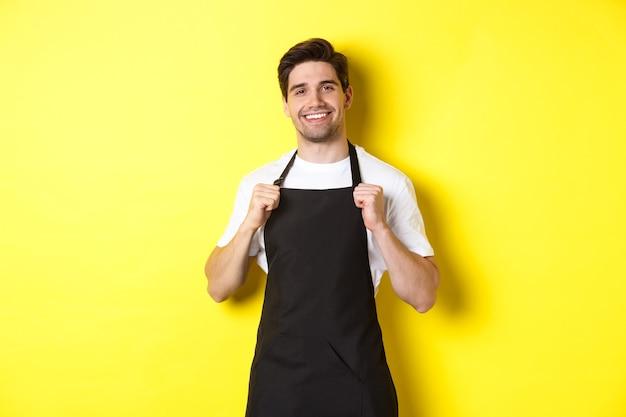 Pewny siebie barista w czarnym fartuchu stojący przed żółtą ścianą kelner uśmiecha się i wygląda na szczęśliwego.