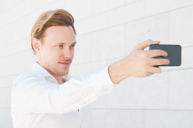 Pewny siebie biznesmen biorąc selfie zdjęcie na zewnątrz